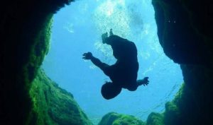 A diver sinks into the spring water at Jacobs well