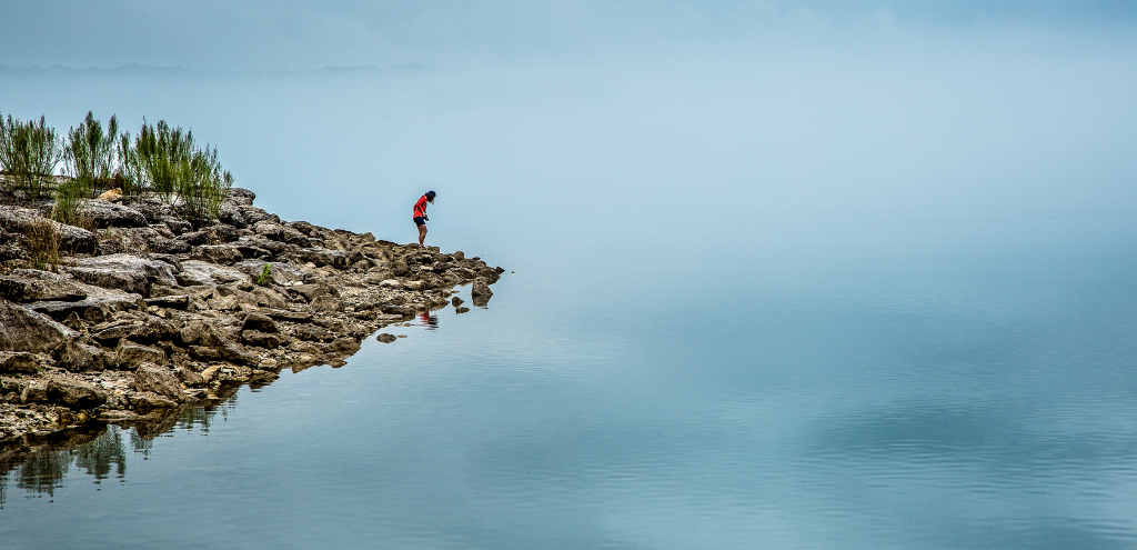 Person standing on the rocky edge of a misty lake