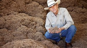 Bill Nieman sits in front of a pile of native seeds