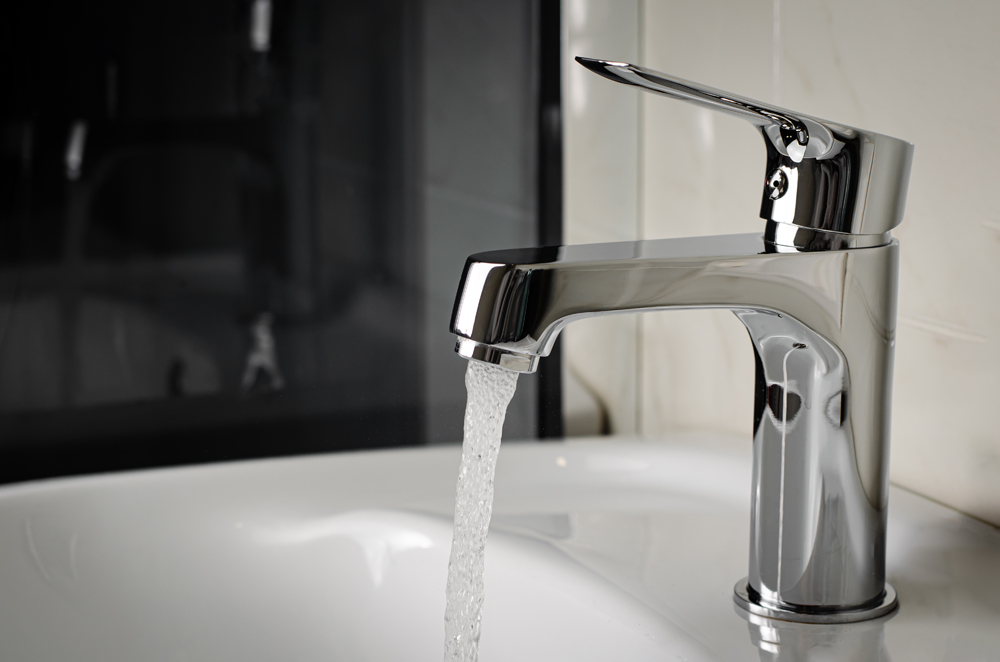 Water Flows From The Tap Or Faucet In Bathroom.