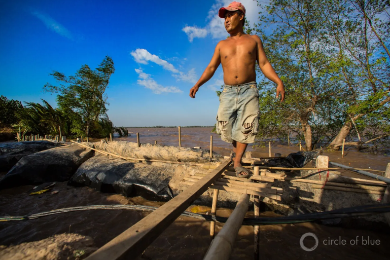 A Farmer In The Mekong Delta Uses Plastic, Mud, And Sticks To Hold Back The Rising Sea.