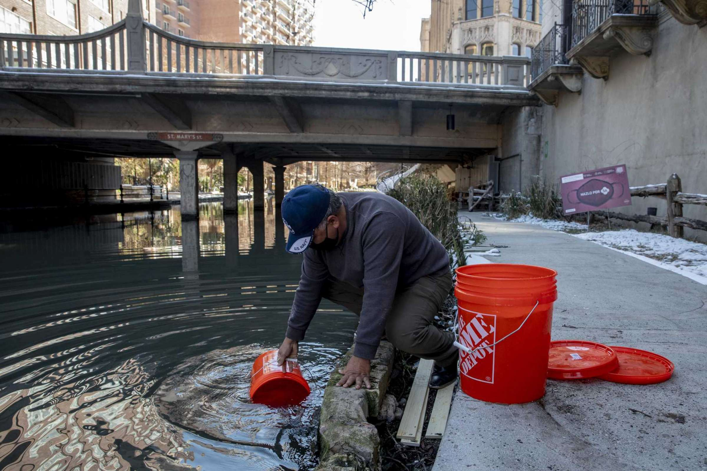 A Man Taking Water From The San Antonio Riverwalk During Winter Storm For Water