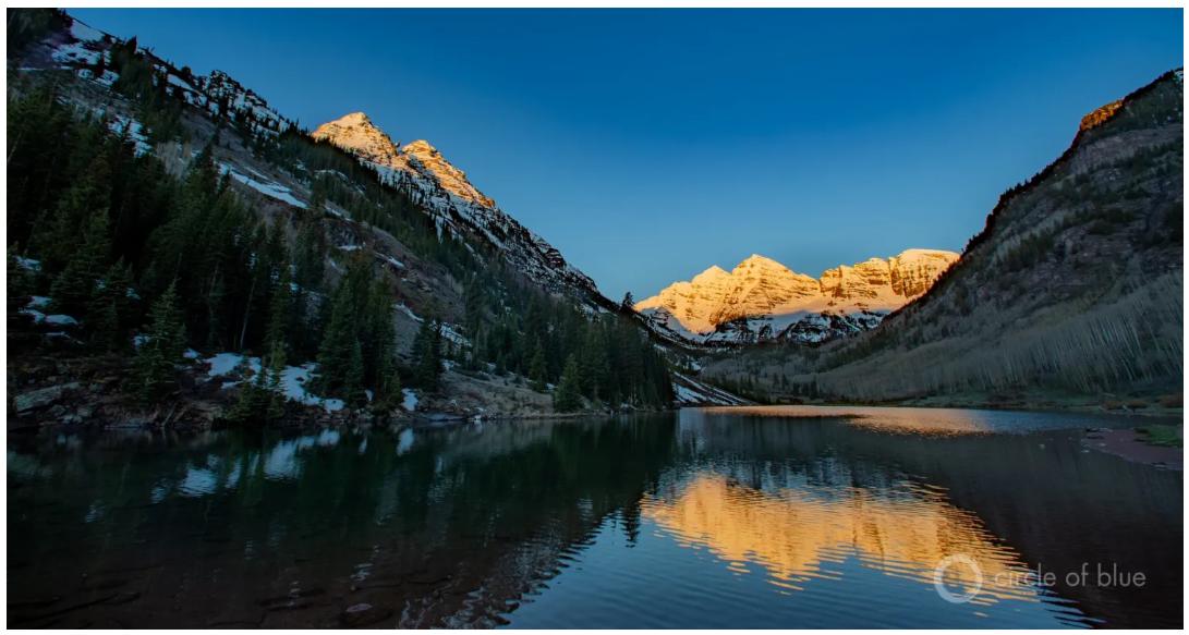Colorado River With The Sun Setting On Mountain Peaks In The Background, Pockets Of Snow Scattered.
