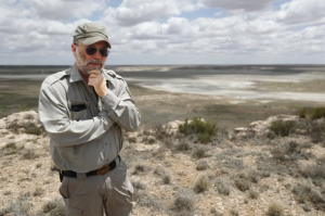 Biologist Jude Smith stands on a bluff overlooking an empty saline lake at the Muleshoe National Wildlife Refuge