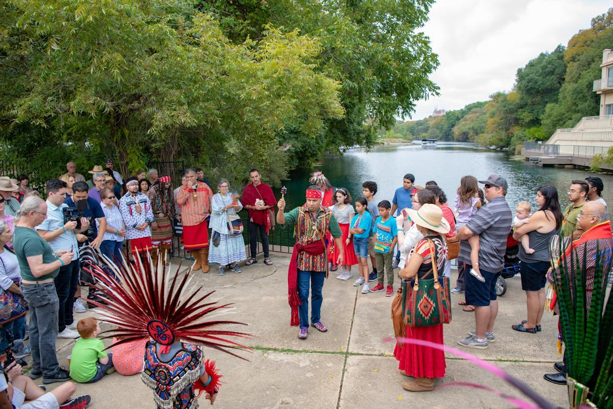 A Crowd Of People Gather For A Blessing Of The San Marcos Headwaters, Several Members Including The Main Speaker Are Dressed In Indigenous Regalia
